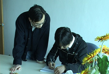 An SGS auditor (right) writing an Audit Report draft.